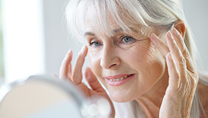 Older woman looking at fine lines in mirror