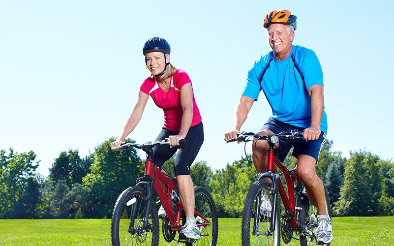 Older man and woman riding bikes together