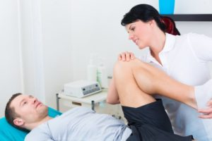 physical therapist bending patient knee