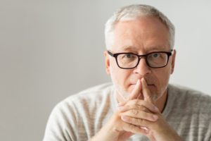 man folded hands glasses